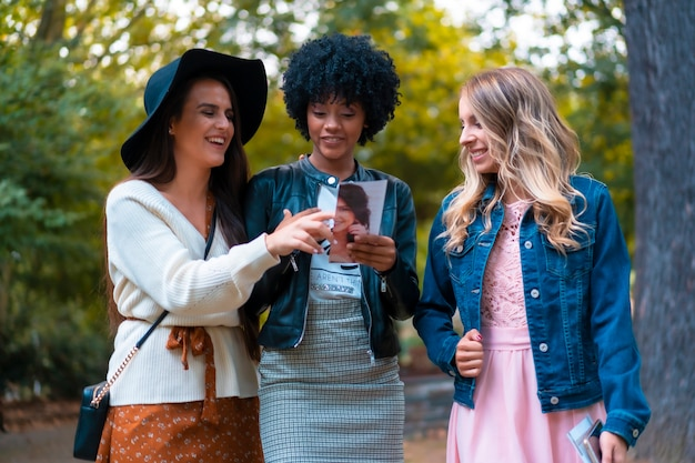 Levensstijl. drie jonge vrienden die een park bezoeken en een flyer, een blonde, een brunette en een latijns meisje met afrohaar bekijken