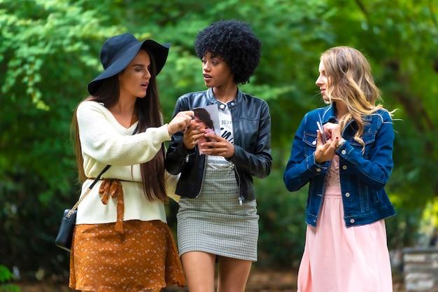 Levensstijl. drie jonge vrienden lachen in een park en kijken naar een flyer, een blonde, een brunette en een latijns meisje met afrohaar
