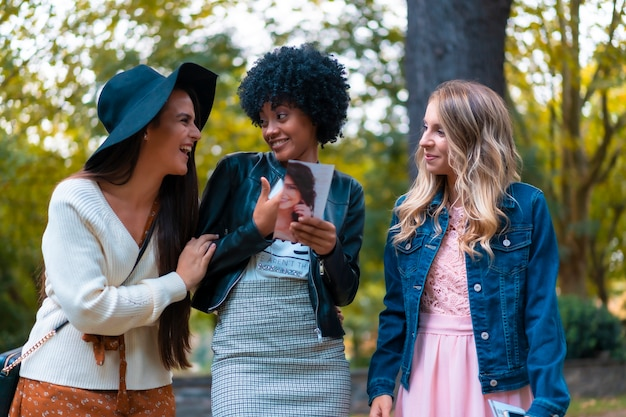 Levensstijl. drie leuke jonge vrienden die een park bezoeken, een blondine, een brunette en een latijns meisje met afrohaar
