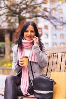 Levensstijl, een blanke brunette die in de stad winkelt met papieren zakken en een afhaalkoffie, glimlachend zittend op de bank