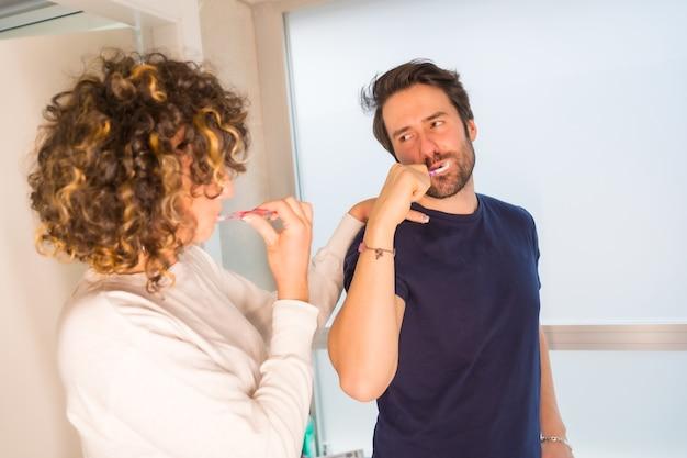 Levensstijl, een jong kaukasisch stel in pyjama's die hun tanden heel gelukkig poetsen
