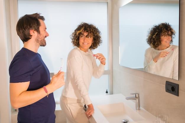 Levensstijl, een jong kaukasisch stel in pyjama's die hun tanden poetsen in de badkamer, elkaar heel blij aankijken