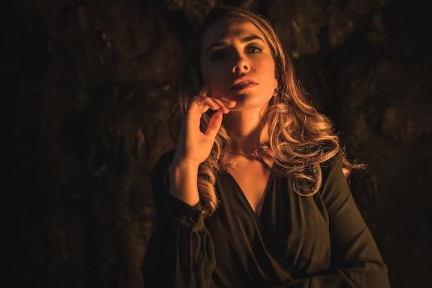 Levensstijl een jonge blanke blonde in een zwarte jurk in een grot verlicht met geel licht portret van de jonge vrouw die geniet van de herfstmiddag