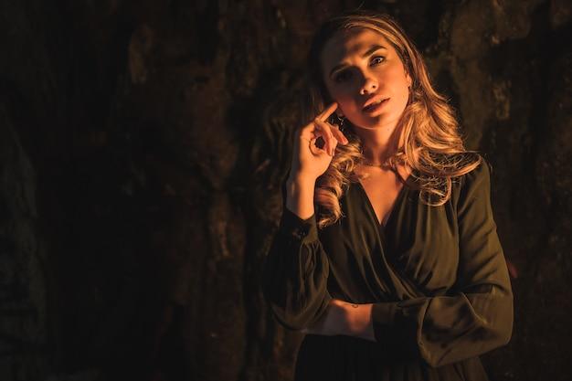 Levensstijl een jonge blanke blonde in een zwarte jurk in een grot verlicht met geel licht zeer verleidelijk portret van het model