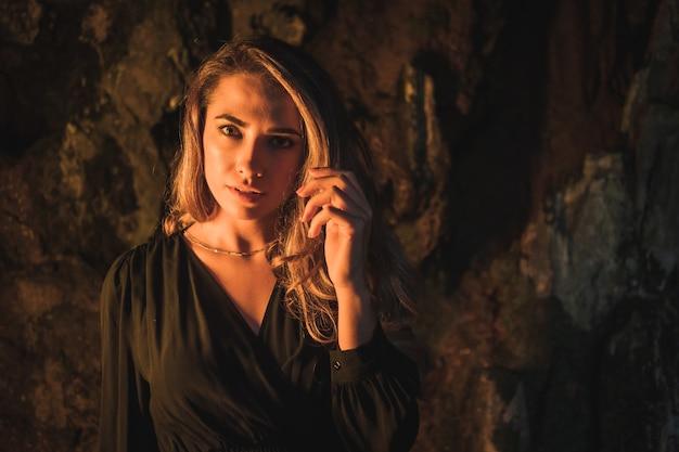 Levensstijl een jonge blanke blonde in een zwarte jurk in een grot verlicht met geel licht zeer verleidelijke pose van het model