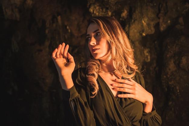 Levensstijl een jonge blanke blonde in een zwarte jurk in een grot verlicht met geel licht