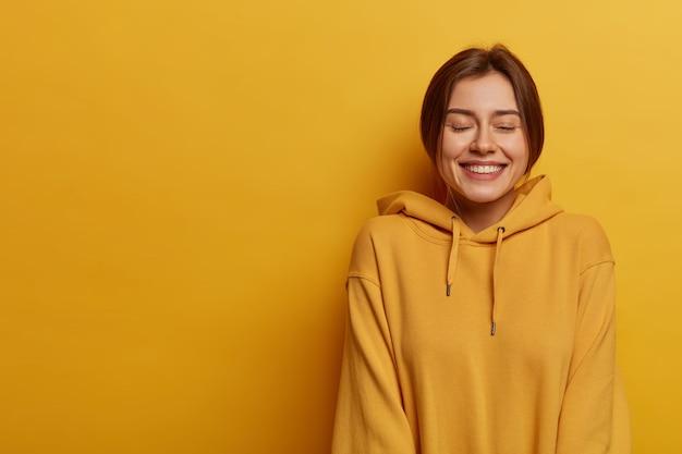 Levensstijl en emoties concept. blije vrouw sluit ogen en grinnikt, lacht en heeft plezier, draagt een sweatshirt, toont witte tanden