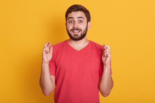 Levensstijl en mensen concept. beeld en aantrekkelijke kerel die op speciaal ogenblik wachten, jonge gebaarde mens die rode toevallige t-shirt dragen