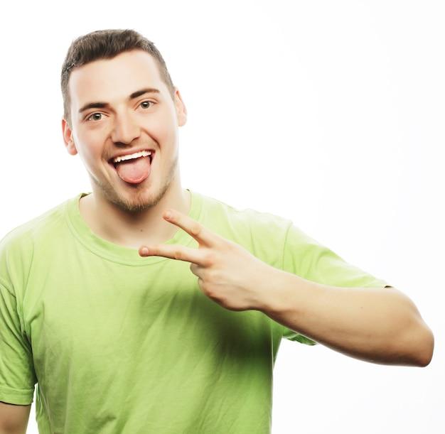 Levensstijl en mensen concept: casual jongeman toont het gebaar van de overwinning terwijl hij lacht voor de camera met een hand in zijn zak. geïsoleerd op witte achtergrond