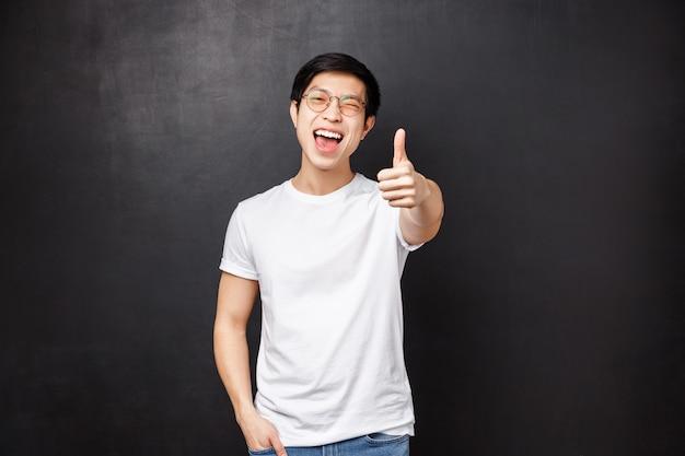 Levensstijl en mensen concept. de gelukkige en tevreden jonge aziatische moderne kerelklant verliet onder de indruk en tevreden na het bijwonen van geweldig concert, toont duim omhoog in goedkeuring en knipoogt met vreugde
