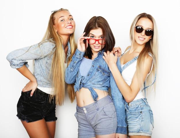 Levensstijl en mensen concept: fashion portret van drie stijlvolle sexy meisjes beste vrienden, op witte achtergrond. fijne tijd voor plezier.