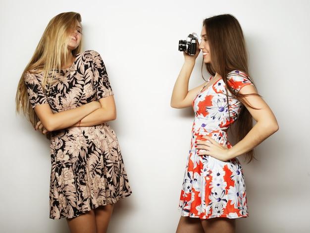 Levensstijl en mensen concept: gelukkige meisjesvrienden die enkele foto's nemen, op grijs