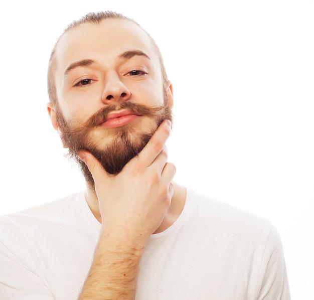 Levensstijl en mensen concept: jonge, bebaarde man, casual stijl, close-up. geïsoleerd op een witte achtergrond.