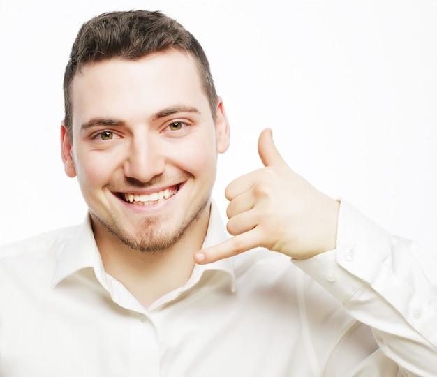 Levensstijl en mensen concept: jonge knappe man in overhemd gebaren mobiele telefoon in de buurt van zijn gezicht en glimlachen terwijl staande tegen witte ruimte