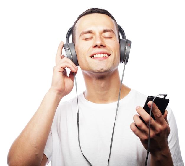 Levensstijl en mensen concept: jonge man genieten van muziek op zijn koptelefoon, luisteren naar muziek tegen een witte achtergrond en glimlachen. vrolijke tijd.