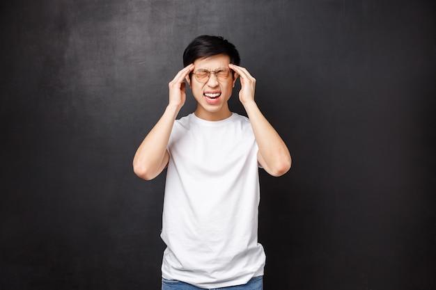 Levensstijl en mensen concept. knappe jonge aziatische mannelijke student had gisteren een geweldig feest, kater voelen, tempels aanraken als pijnlijke hoofdpijn, ziek werd, migraine had,