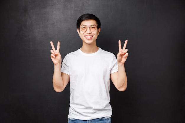 Levensstijl en mensen concept. leuke jonge aziatische hipster man in wit t-shirt en zonnebril maken kawaii vredestekens en zorgeloos glimlachen, ontspannen op feestje, genieten van de koele lentedag