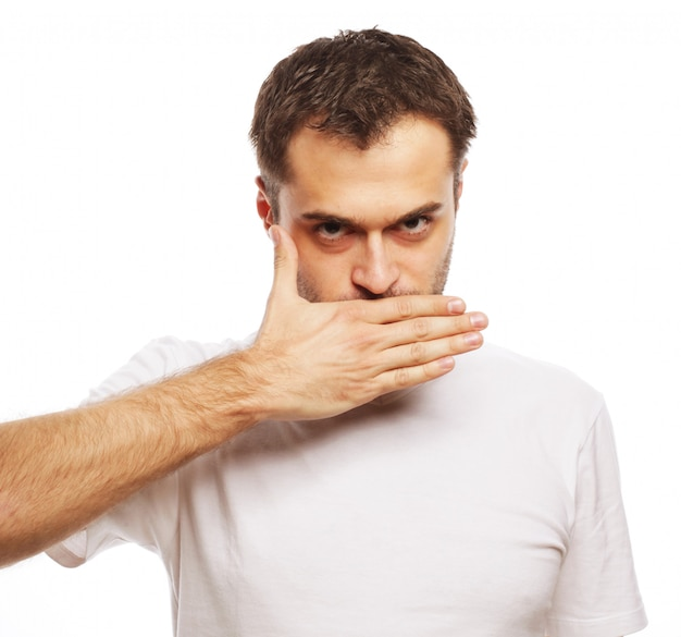 Levensstijl en mensenconcept: geschokte jonge man die mond bedekt met handen en camera bekijkt terwijl hij tegen witte ruimte staat