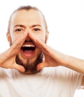 Levensstijl en mensenconcept: goed nieuws! jonge, bebaarde man die hand in de buurt van de mond houdt en schreeuwt terwijl hij tegen witte ruimte staat.