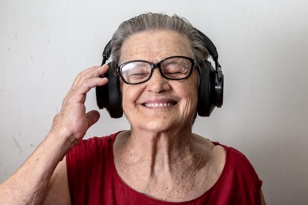 Levensstijl en mensenconcept: grappige oude dame het luisteren muziek en het dansen op witte achtergrond. bejaarde die glazen draagt die aan muziek dansen die op zijn hoofdtelefoons luisteren.
