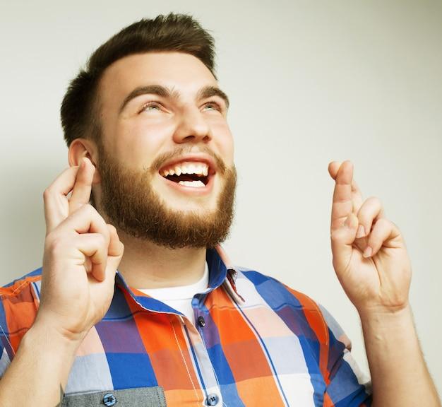 Levensstijl en mensenconcept: wachten op een speciaal moment. portret van een jonge, bebaarde man in overhemd die vingers houden terwijl hij tegen witte ruimte staat. hipster-stijl en positieve emoties.