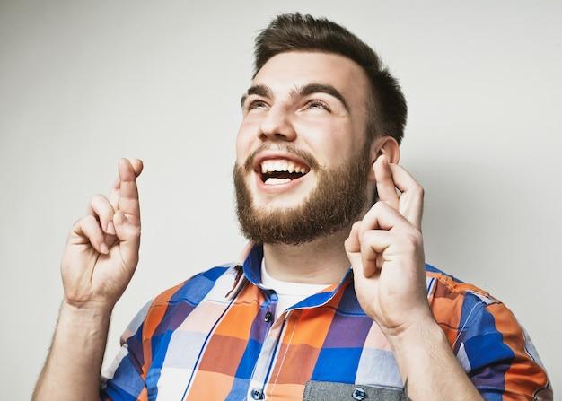 Levensstijl en mensenconcept: wachten op een speciaal moment. portret van een jonge, bebaarde man in shirt die vingers houdt terwijl hij tegen een witte achtergrond staat. hipsterstijl en positieve emoties.