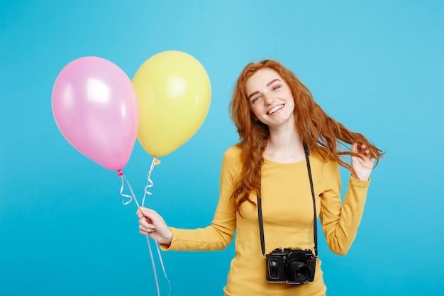 Levensstijl en partij concept close-up portret jonge mooie aantrekkelijke gember rood haar meisje met kleurrijke ballon en vintage camera blauwe pastel muur kopie ruimte Premium Foto