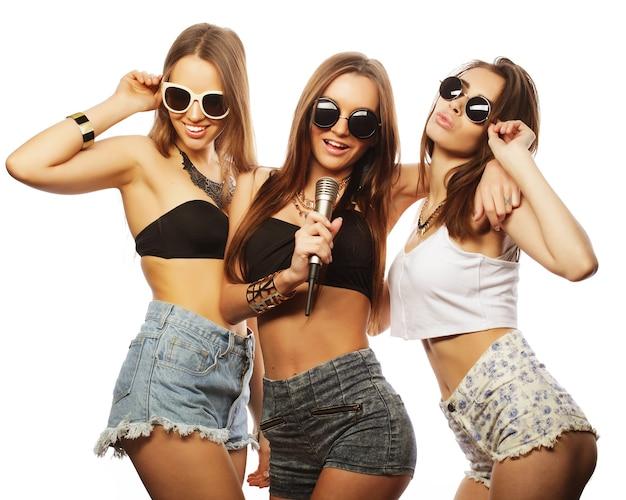 Levensstijl, geluk, emotioneel en mensenconcept: groep jonge vrouwen die plezier hebben bij karaoke