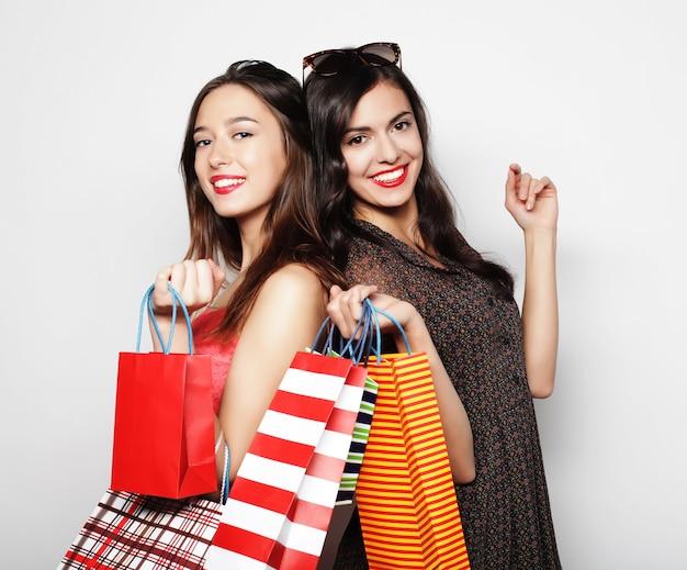 Levensstijl, geluk, emotioneel en mensenconcept: mooie tienermeisjes met boodschappentassen, over witte achtergrond