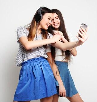 Levensstijl, geluk, emotioneel en mensenconcept. schoonheid hipster meisjes met een microfoon zingen en foto maken met smartphone op wit