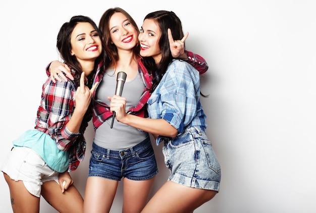 Levensstijl, geluk, emotioneel en mensenconcept: schoonheid hipstermeisjes met een microfoon die zingt en plezier heeft