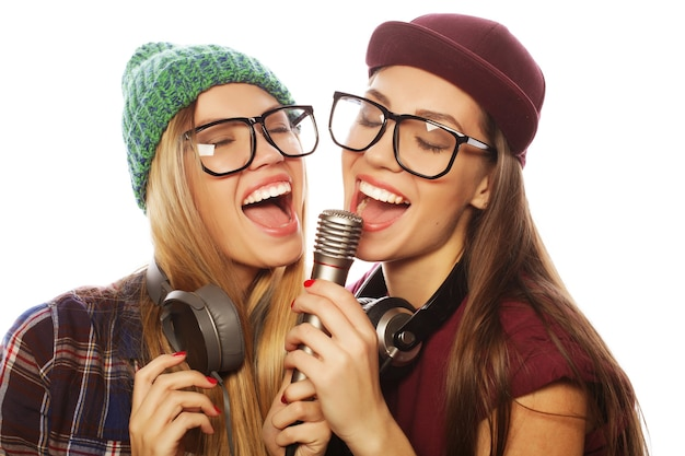 Levensstijl, geluk, emotioneel en mensenconcept: twee hipstermeisjes van schoonheid met een microfoon die zingt en plezier heeft