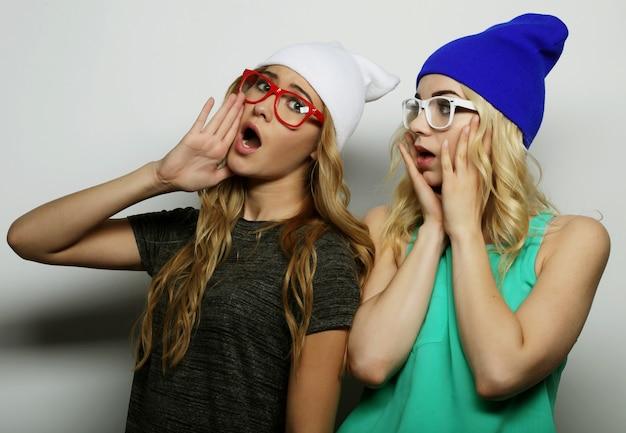 Levensstijl, geluk, emotionele en mensen concept: close-up fashion lifestyle portret van twee jonge hipster meisjes beste vrienden, lichte make-up en soortgelijke trendy hoeden dragen, grappige gezichten maken.