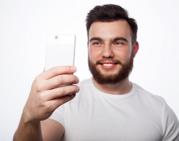 Levensstijl, geluk en mensen concept: jonge, bebaarde man met mobiele telefoon in de hand tegen grijze ruimte.