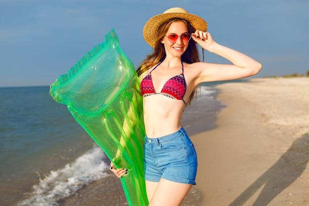 Levensstijl heldere zomer positief portret van jonge mooie hipster vrouw met plezier op het strand
