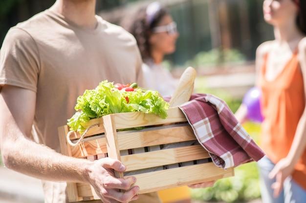 Levensstijl. houten kist met verse groenten en heerlijk brood in handen van man voor picknick en vriendin achter buitenshuis