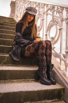 Levensstijl in de stad, blanke brunette in een korte zwarte jurk, een baret en met geruite kousen zittend genietend van de vakantie in de zomer