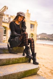 Levensstijl in de stad, poseren van een brunette blanke in een korte zwarte jurk en geruite kousen naast een strand op vakantie in de zomer