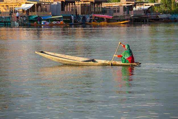 Levensstijl in het dal-meer, lokale mensen gebruiken shikara, een kleine boot voor transport in het meer van srinagar, de staat jammu en kasjmir, india. indiase vrouw op een boot