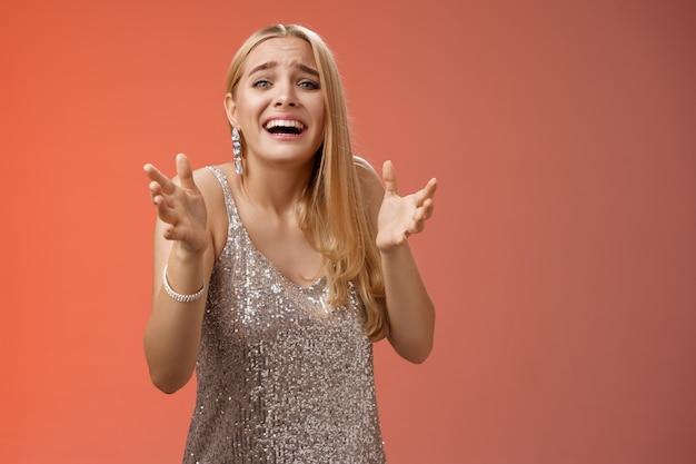 Levensstijl. in paniek, boos, ellendig, diepbedroefd blond meisje huilen handen opsteken smeken niet kapot gaan vriendje kijken verdriet verdrietig freak-out staande verwoeste rode achtergrond tijdens feestje.