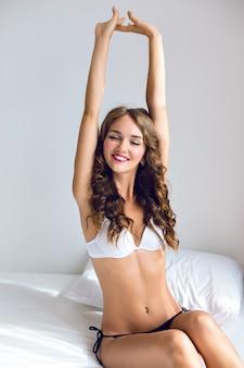 Levensstijl indoor mode portret van vrouw met geweldig slank fit sexy lichaam, poseren op het bed in de ochtendtijd, eenvoudige casual lingerie dragen, ontspannen en genieten van zonnige dag.