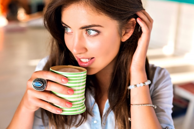 Levensstijl indoor portret van jonge brunette vrouw die zich voordeed op stadscafetaria genieten van haar lekkere warme koffie in de ochtend