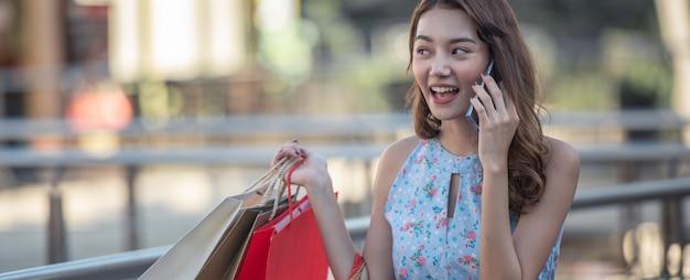 Levensstijl jonge gelukkige vrouw met boodschappentas en praten met vriend op mobiele telefoon met genieten van bij winkelcentrum.