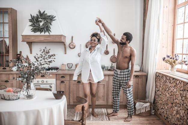 Levensstijl. jonge volwassen afro-amerikaanse shirtless op blote voeten dansen met lachende vrouw in wit overhemd in comfortabele keuken