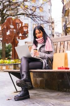 Levensstijl, kaukasisch donkerbruin meisje dat met laptop in een park werkt, zittend op een bankje