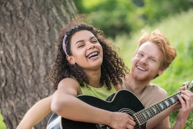 Levensstijl. lachend gelukkig jong mooi krullend meisje met gitaar en roodharige man in vrijetijdskleding die rust heeft op een zomerdag in de natuur