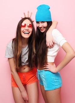 Levensstijl, mensen, tieners en vriendschap concept - gelukkig lachend mooie tienermeisjes of vrienden knuffelen op roze achtergrond