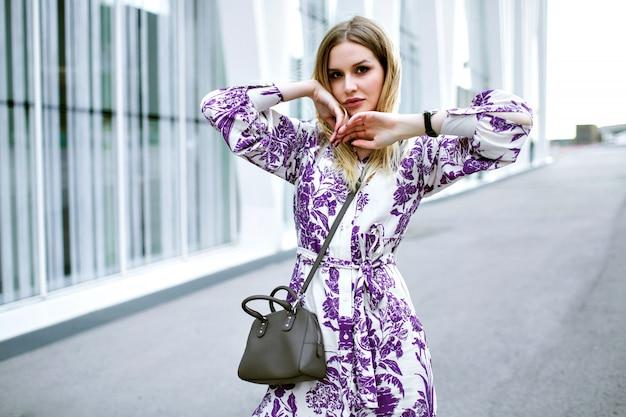 Levensstijl mode portret van stijlvolle mooie blonde vrouw die zich voordeed op straat in de buurt van het moderne zakencentrum, het dragen van glamour bloemen jurk tas en accessoires, zachte getinte kleuren.