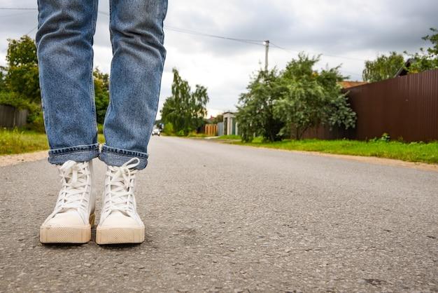 Levensstijl. moderne jonge vrouw in een stijlvolle blauwe spijkerbroek in modieuze witte sneakers staat op weg. stijlvolle damesschoenen. jeugdstijl. close-up van vrouwelijke benen in trendy schoenen.