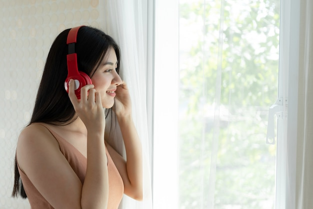 Levensstijl mooie aziatische vrouw schattig meisje voelt gelukkig genieten van het luisteren naar muziek met koptelefoon koptelefoon op witte slaapkamer